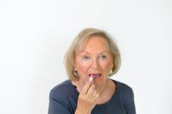 Femme supérieure appliquant une nuance naturelle de rouge à lèvres Photo stock