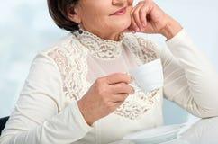 Femme supérieure appréciant la cuvette de coffe Photos stock