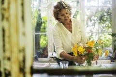 Femme supérieure arrangeant les fleurs fraîches images libres de droits