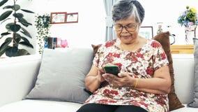 Femme supérieure asiatique à l'aide du téléphone intelligent à la maison, grand-mère heureuse avec la technologie à disposition l banque de vidéos