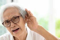 Femme supérieure asiatique écoutant par des hand's jusqu'à l'oreille, ayant la difficulté dans l'audition, femme agée dur à ent photos stock
