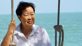 Femme supérieure asiatique jouant l'oscillation avec le backgr d'horizon d'océan d'océan Images libres de droits
