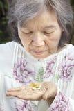 Femme supérieure asiatique regardant des pilules Photos libres de droits