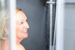 Femme supérieure attirante de sourire prenant une douche Photos libres de droits