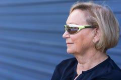 Femme supérieure attirante utilisant les lunettes de soleil à la mode Images stock
