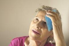 Femme supérieure avec de la glace sur la tête pour le mal de tête photo stock