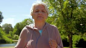 Femme supérieure avec des écouteurs fonctionnant en parc d'été banque de vidéos