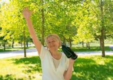 Femme supérieure avec des jumelles en parc Photo libre de droits