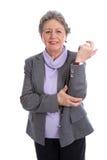 Femme supérieure avec douleur dans le poignet - une femme plus âgée d'isolement sur le blanc Image stock