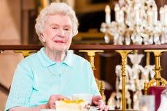 Femme supérieure avec du café et le gâteau en café Photographie stock libre de droits
