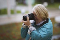 Femme supérieure avec l'appareil-photo de photo au jour d'été en parc, extérieur Photo stock