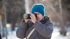 Femme supérieure avec l'appareil-photo de photo au jour d'hiver ensoleillé, extérieur Photographie stock