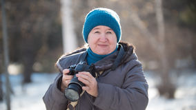 Femme supérieure avec l'appareil-photo de photo au jour d'hiver, extérieur Photo libre de droits