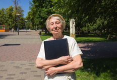 Femme supérieure avec l'ordinateur portable en parc Photo libre de droits