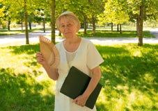 Femme supérieure avec l'ordinateur portable en parc Photographie stock libre de droits