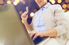 Femme supérieure avec l'ordinateur portable et la carte de crédit Photo libre de droits
