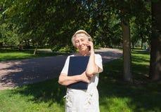 Femme supérieure avec l'ordinateur portable utilisant un téléphone portable Photographie stock