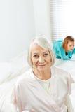 Femme supérieure avec la femme de ménage à la maison photo stock