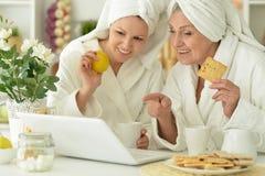 Femme supérieure avec la fille avec l'ordinateur portable Images stock