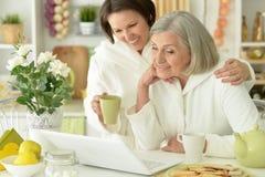Femme supérieure avec la fille avec l'ordinateur portable Image stock