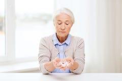 Femme supérieure avec la médecine à la maison Photos stock