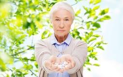 Femme supérieure avec la médecine à la maison Images stock