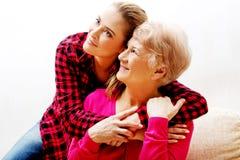Femme supérieure avec la petite-fille ou la fille étreignant sur le divan Images stock