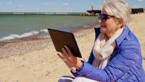 Femme supérieure avec la tablette sur la plage banque de vidéos