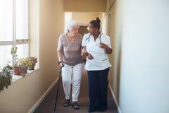 Femme supérieure avec le bâton de marche aidé par une infirmière féminine a Photographie stock