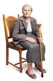 Femme supérieure avec le bâton de marche se reposant sur la chaise Images libres de droits