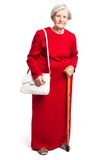 Femme supérieure avec le bâton de marche se tenant sur le blanc Image stock