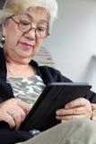 Femme supérieure avec le comprimé Photos libres de droits