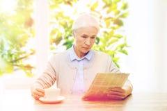 Femme supérieure avec le journal de lecture de café Images stock