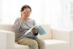 Femme supérieure avec le livre dans le salon Image libre de droits