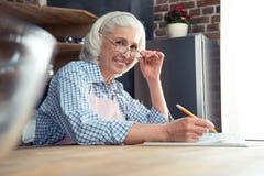 Femme supérieure avec le livre de cuisine Photo libre de droits