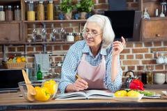 Femme supérieure avec le livre de cuisine Photos stock