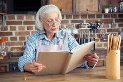 Femme supérieure avec le livre de cuisine Images libres de droits