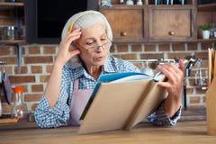 Femme supérieure avec le livre de cuisine Image stock