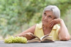 Femme supérieure avec le livre ouvert Photographie stock libre de droits