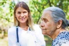 Femme supérieure avec le médecin en parc Image libre de droits