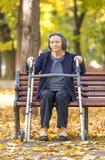 Femme supérieure avec le marcheur s'asseyant sur le banc dehors Photos stock