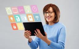 Femme supérieure avec le PC de comprimé utilisant l'appli à la maison futé photographie stock