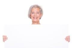 Femme supérieure avec le signe Photos stock