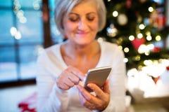 Femme supérieure avec le smartphone au temps de Noël Image stock