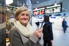 Femme supérieure avec le smartphone dans le couloir du souterrain Photo libre de droits