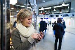 Femme supérieure avec le smartphone dans le couloir du souterrain Images libres de droits