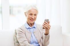Femme supérieure avec le smartphone et les écouteurs à la maison image stock