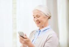 Femme supérieure avec le smartphone textotant à la maison Images stock