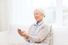Femme supérieure avec le smartphone textotant à la maison Images libres de droits