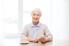 Femme supérieure avec le smartphone textotant à la maison Image stock